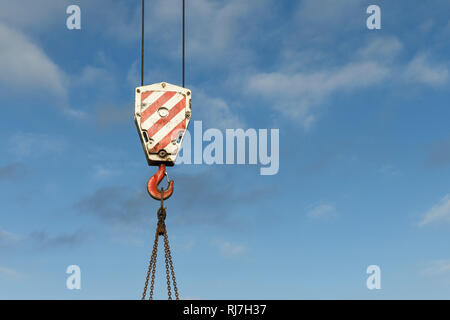 A heavy duty crane load block against a blue sky - Stock Image