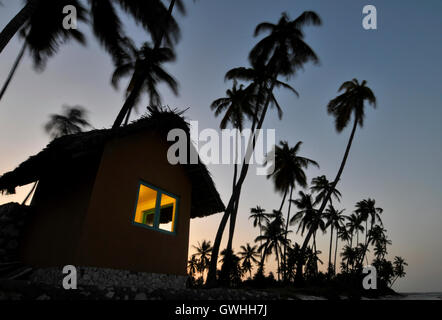 A lone hut with trees silhouetted at sunset. - Stock Image