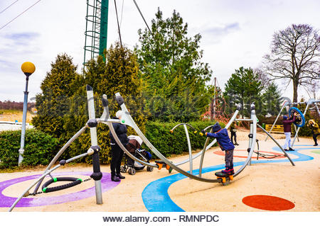 Poznan, Poland - February 10, 2019: Kid standing on a new skate track equipment on a modern playground at the Malta park on a cloudy day. Mother is wa - Stock Image