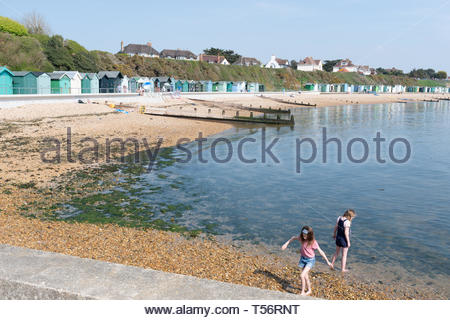 Two children (young girls) enjoying a sunny spring day on the beach at Hill Head in Hampshire, UK - Stock Image