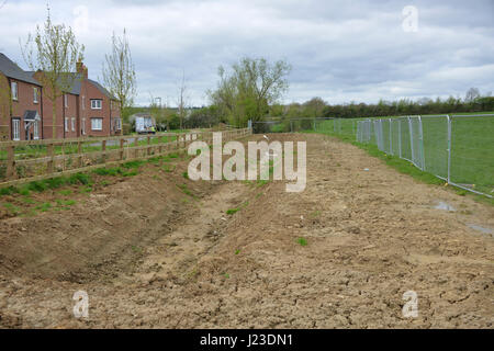 Drainage ditch to prevent flooding close to a new housing development in the north Oxfordshire village of Hook Norton - Stock Image