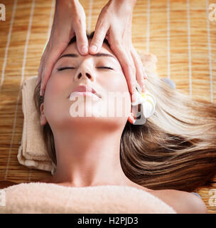 Woman during face massage, masseuse doing facial massage for a beautiful calm female, beauty and healthy treatment - Stock Image