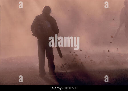 Two men using backpack leafblowers in silhouette - Stock Image