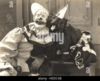 Clown posing with dog dressed in clown costume - Stock Image