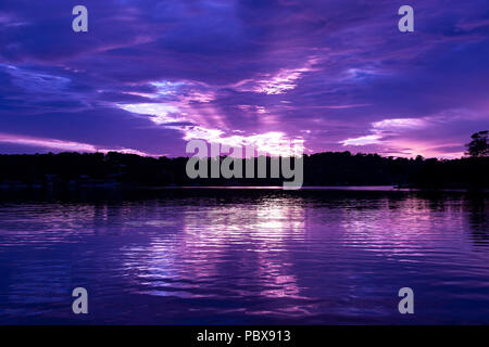 A striking vivid Purple  colored cloudy panoramic sunrise seascape over sea water with water reflections. Queensland, Australia. - Stock Image