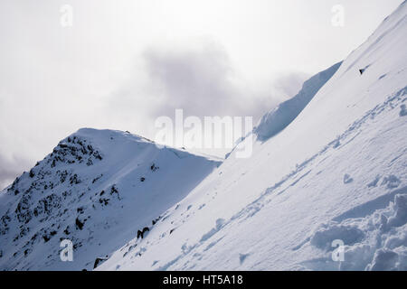 View to Y Garn summit from north east ridge with snow cornice blocking path in Snowdonia National Park mountains. - Stock Image