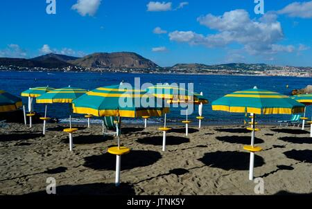 Beautiful beach  of Baia, Naples in Italy.Before the day ends in the resort umbrellas standing in the beach adding beautiful colours to the landscape - Stock Image