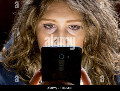Closeup of a beautiful young caucasian woman with long wavy hair, eyes staring at the mobile phone in her hands. - Stock Image