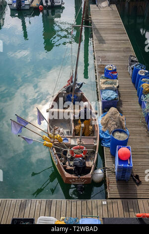 Brighton Marina Views UK - Fisherman working on his nets in small fishing boat at East Jetty - Stock Image