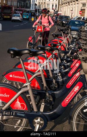 Female City Cyclist with TFL Santander sponsored London red rental hire bikes in Southwark Street with female cyclist wearing a helmet about to start her bicycle hire ride from the TFL Santander bike terminal docking station. Transport for London Southwark London UK - Stock Image