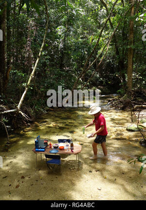 Picnic table with BBQ set up in rainforest creek, Dinden National Park, near Cairns, Queensland, Australia. No MR or PR - Stock Image