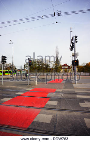 Poznan, Poland - November 1, 2018: Zebra crossing with red marked bicycle path and red lights on the Roosevelta street in the city center. - Stock Image