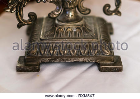 Close up of a metal candle holder bottom on a white cloth in soft focus. - Stock Image