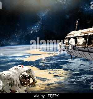 A team of astronauts perform work on a space station while orbiting a large, Earth-like planet. The nearby star - Stock Image