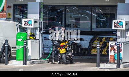 Motorbiker refilling his bike in the Asda petrol filling station in Bangor, Northern Ireland - Stock Image