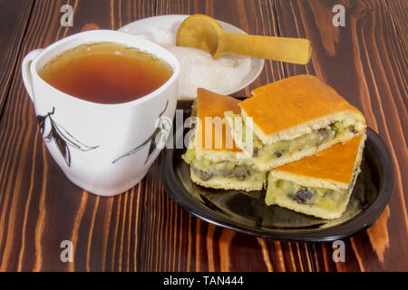 Still life with tea and sliced pies on a plate - Stock Image