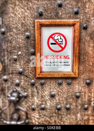 Framed No Smoking sign on an old wooden door. - Stock Image