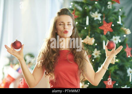 smiling trendy woman in red dress near Christmas tree doing yoga - Stock Image