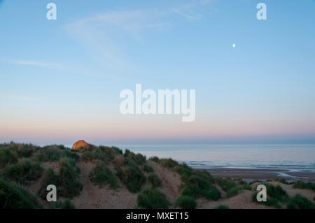 A tent perched on top of a sand dune at dawn - Stock Image
