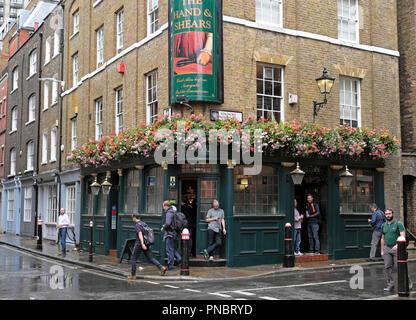 People drinking outside the Hand & Shears pub in the rain on Cloth Fair on Middle Street,  Smithfield London EC1 England UK  KATHY DEWITT - Stock Image