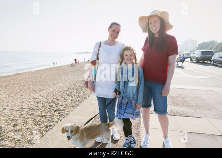 Portrait smiling lesbian couple with daughter and dog on sunny beach boardwalk - Stock Image