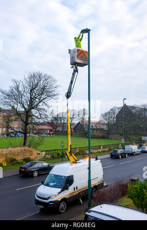 Man on an Hydraulic Hoist carrying out a repair on a street lamp post - Stock Image
