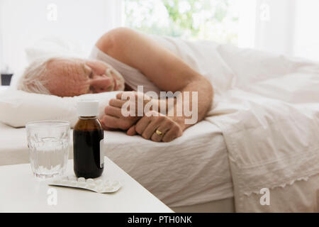Tired senior man sleeping next to night stand with cough syrup and medicine - Stock Image