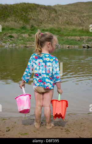 3 year old girl playing at the seaside with two buckets. - Stock Image