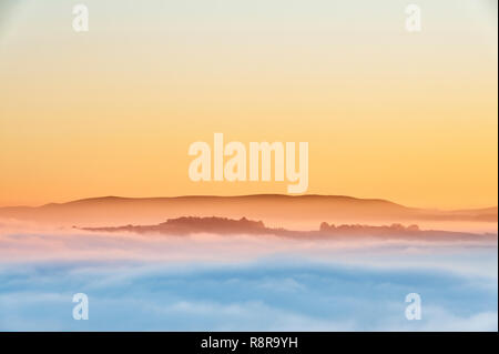 On Stonewall Hill in the Welsh borders near Knighton, UK. Evening view of Hay Bluff and the Black Mountains showing the valleys filled with thick fog - Stock Image