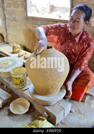 Female Burmese potter on wheel making large ceramic pots in one of the rural villages around Inle Lake in Myanmar - Stock Image