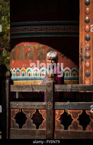 Elderly Bhutanese woman turning large wooden prayer wheel in Trongsa, Bhutan - Stock Image