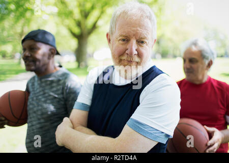 Portrait confident active senior man playing basketball with friends - Stock Image