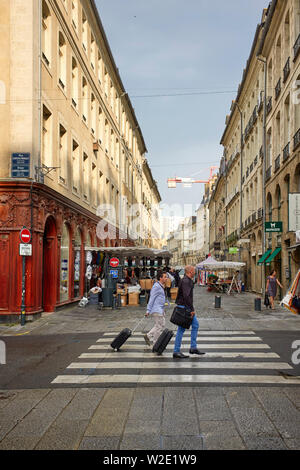 Two men with overnight bags walking as market stalls are being set up on the day of sales at Rennes the capital of Brittany, France - Stock Image