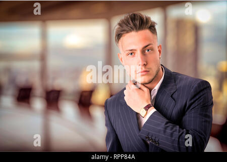 Elegant young man with business suit in office - Stock Image