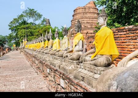 Row of Buddha statue sitting at Wat Yai Chaimongkol temple in Phra Nakhon Si Ayutthaya Historical Park, Ayutthaya - Stock Image