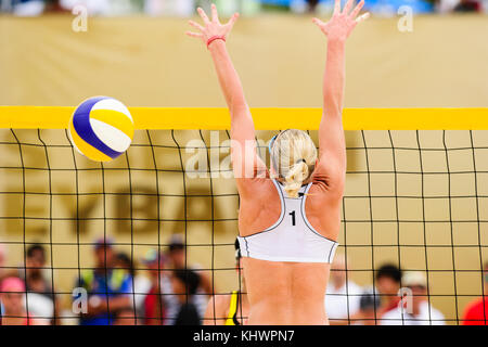 Beach volleyball player is a female beach volleyball player jumping up getting ready to block the ball. - Stock Image