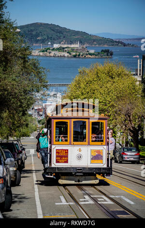 Typical tram climbing a hill overlooking Alcatraz in San Francisco. - Stock Image
