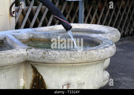 Details of a drinking fountain in Nyon, Switzerland. This fountain is made with light beige concrete and has old black pipe as a tab. - Stock Image