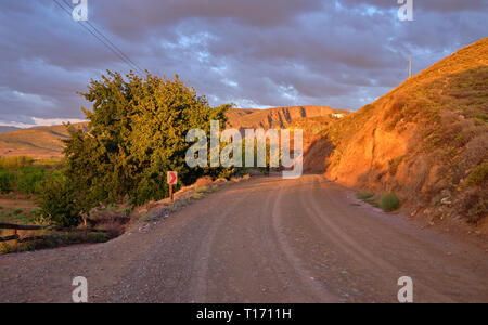 Karoo dirt road leading to a bend in morning light. - Stock Image