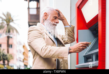 Happy mature man withdraw money from bank cash machine with debit card - Senior male doing payment with credit card in ATM - Stock Image