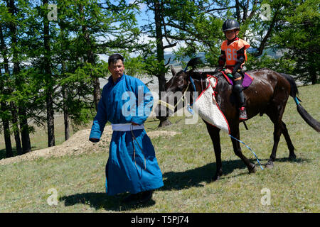 Naadam Festival in Khatgal, Mongolia.Father and sun after the horse racing - Stock Image