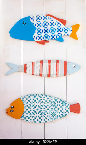 Three Different Folkart Wooden Fish Mounted On A Board - Stock Image