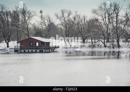 Two fishermen on a fishing dock on a lake in Sedgwick county park in Wichita, Kansas, USA after a late winter snowfall. - Stock Image