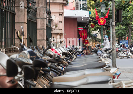 scooters, traffic and communist propaganda symbol in Hanoi, Vietnam - Stock Image