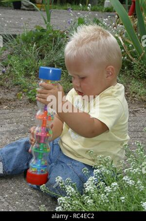Little boy playing with toy in back garden in summer - Stock Image