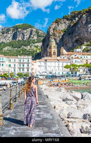 Amalfi, Amalfi coast, Salerno, Campania, Italy. Young woman strolling along the pier of Amalfi village - Stock Image