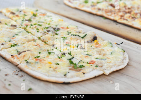 Black Forest speciality called Flammkuchen in south Germany and Tarte flambee in northeast France - vegetarian - on wooden platter - Stock Image