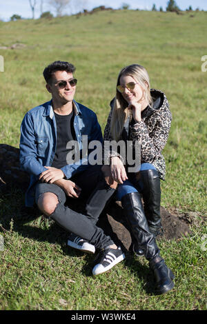 Man and woman sitting in the sun, with jackets and sunglasses on an autumn day - Stock Image