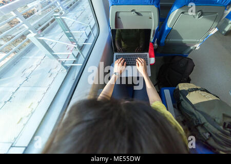 loking in laptop and working during traveling in train - Stock Image
