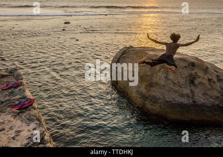 A shocking street entertainer jumps from the walls of the Galle Fort into dangerous waters. Galle, Sri Lanka - Stock Image